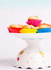 Berry Muffins in colorful cases on a cake stand