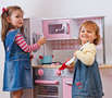 Two girls playing in a toy kitchen pretending cooking