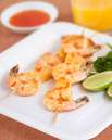 party food recipe of Lime and Chilli Prawns Skewers on a white plate with lime wedges with the dipping sauce and orange juice at the background