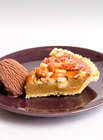 Slice of Butterscotch and Nut Tart on a burgundy plate with a scoop of chocolate icecream