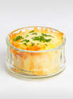 Potato Gratin in a glass ramekin on white background