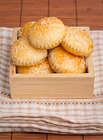 Mini Chicken Mushrooms and Sweet Corn Pies in a wooden box on a broun tablecloth