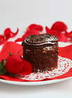 Valentine's Day Recipe of chocolate cake on white plate and red napkin and red rose and red patels