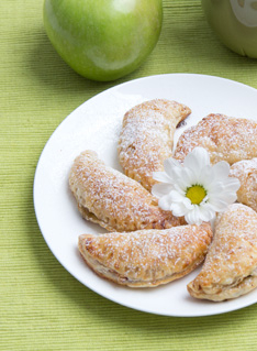 Apple turnovers on a white plate with green background