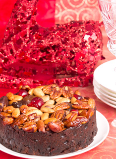 Christmas Cake on a white plate with a crystal glass on the red background