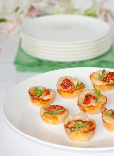 Party Finger food Mini Muffins with semi dried tomatos on a white plate