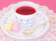 Tea Party, tea cup with rosy tea on a white plate with colorful marshmallow on a white and pink background